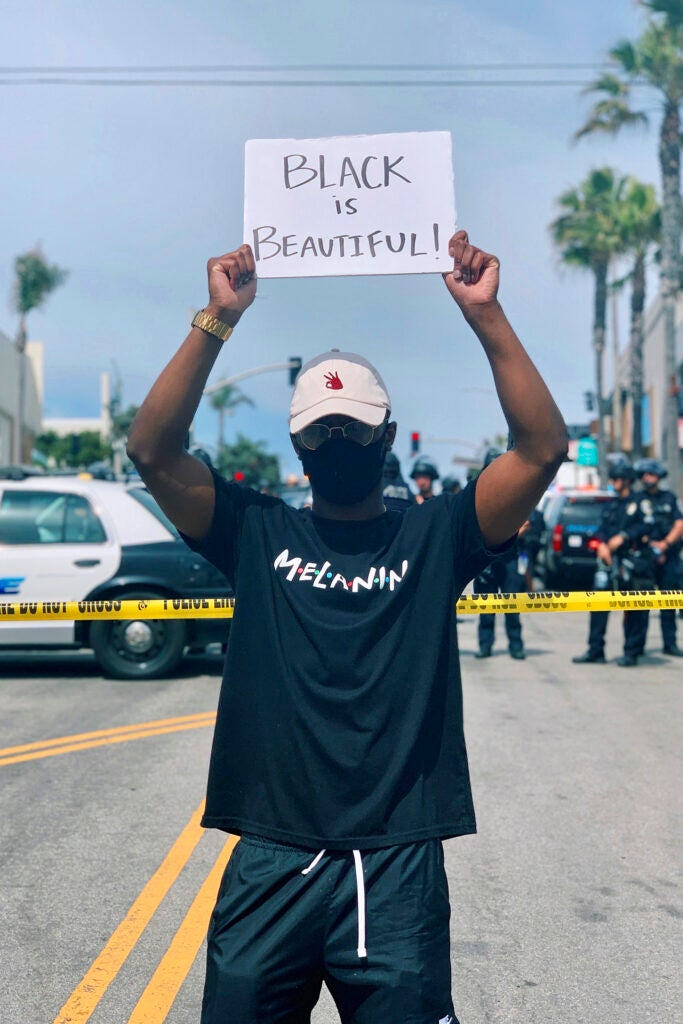 "Elijah DeVaughn holds ""Black is Beautiful"" sign."