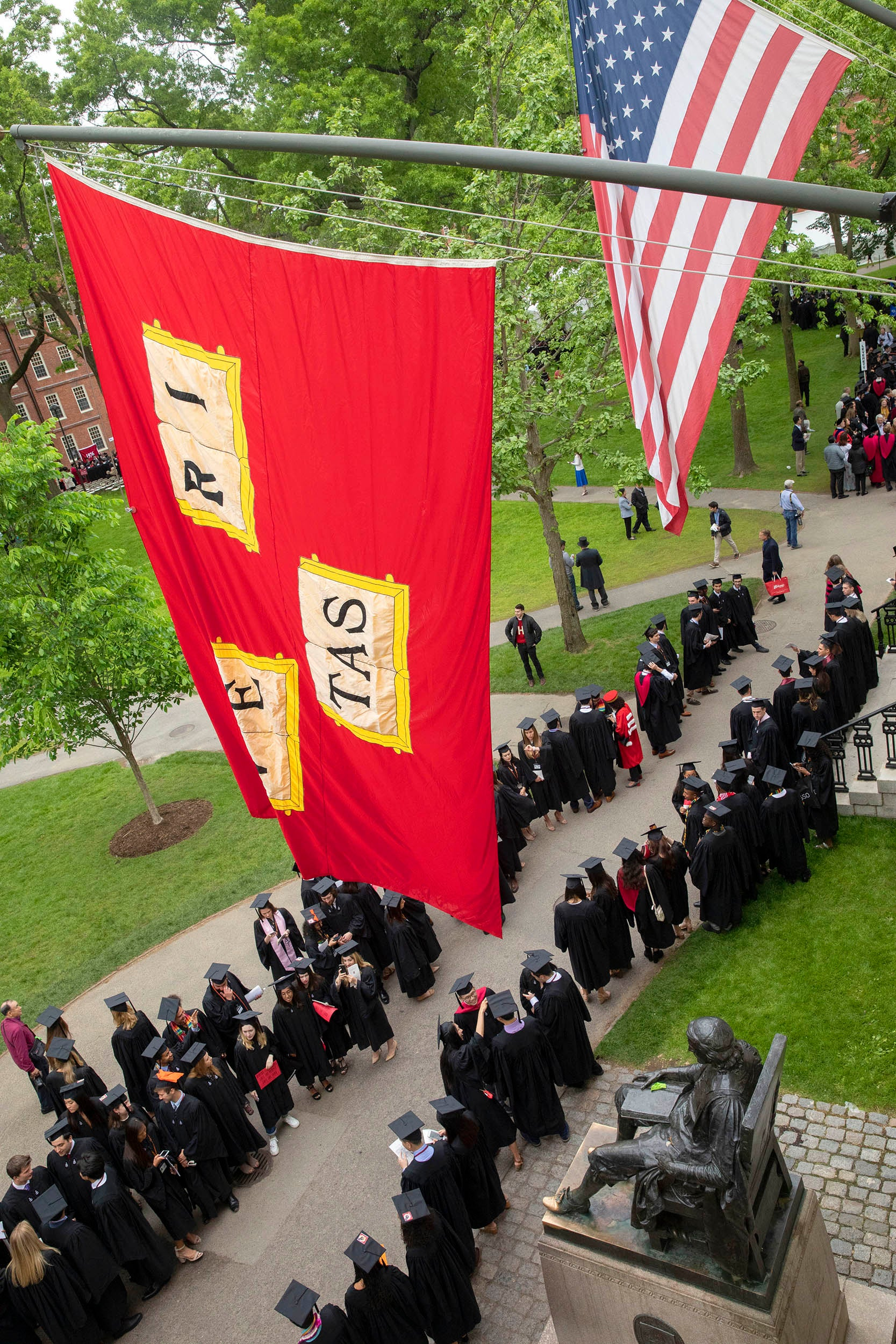 During last year's Morning Exercises at Harvard's 368th Commencement, graduates join the procession beneath veritas flags and the John Harvard Statue in the Tercentenary Theatre.