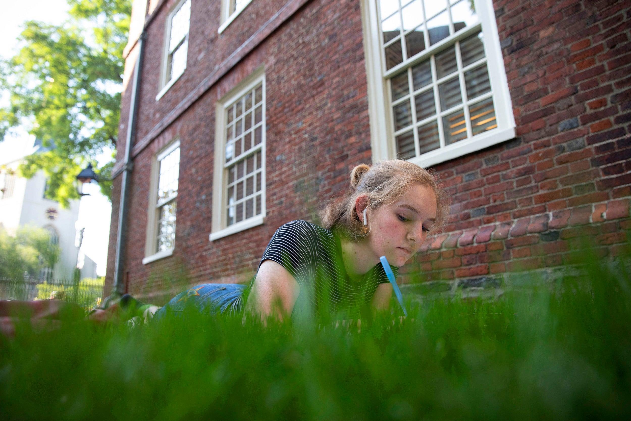 Behind Massachusetts Hall, Grace Carlson '23 enjoys an 80-degree fall day.
