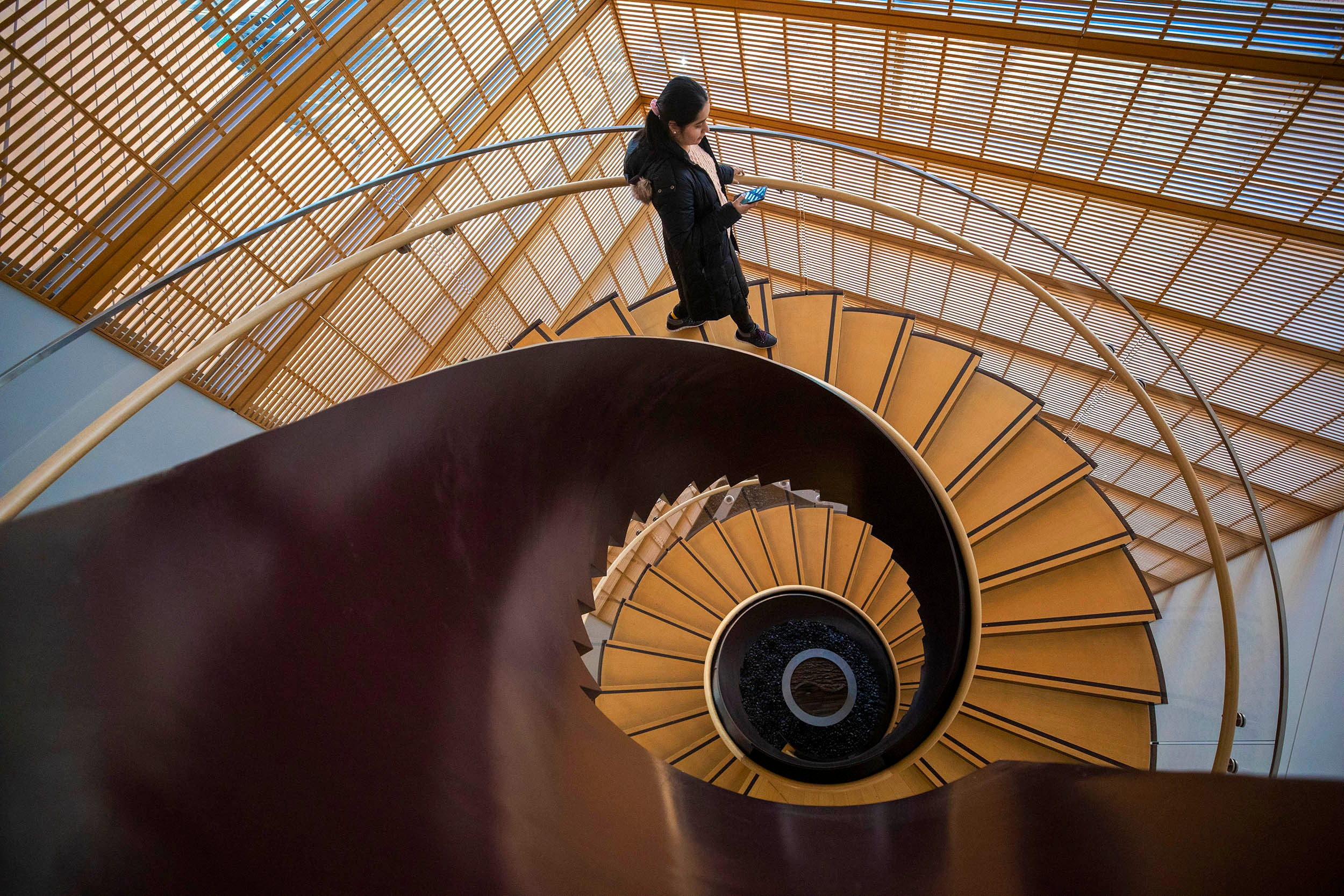 Shubhangi Bhadada appears at the crest of a wave-like spiral staircase at the Center for Government and International Studies.