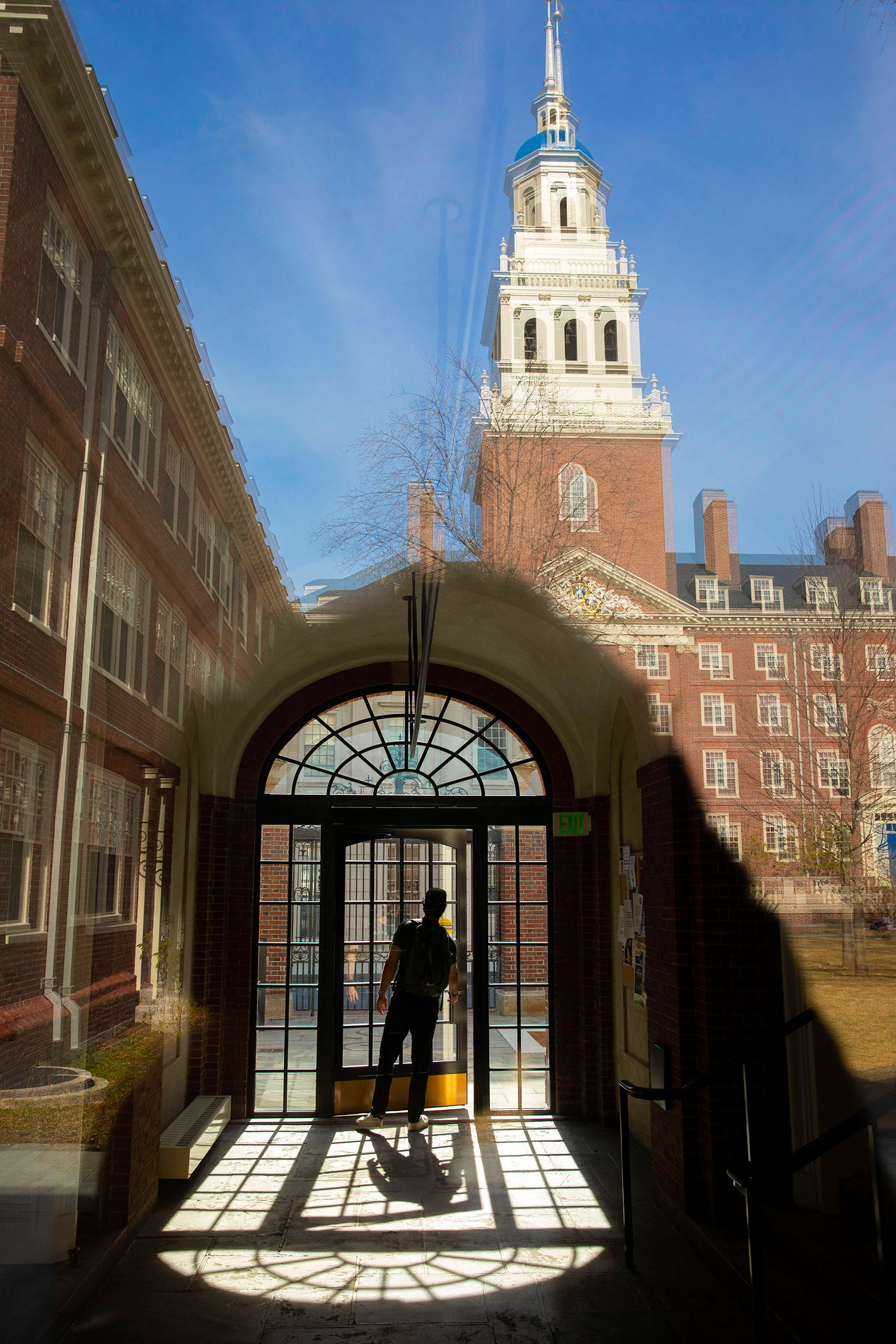 A student is framed by a bay window inside the passageway leading to the dining hall in Lowell House courtyard.