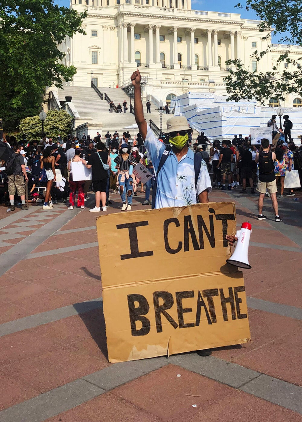 "Glenn Foster holds up a sign saying ""I can't breathe"" in front of the Capitol."