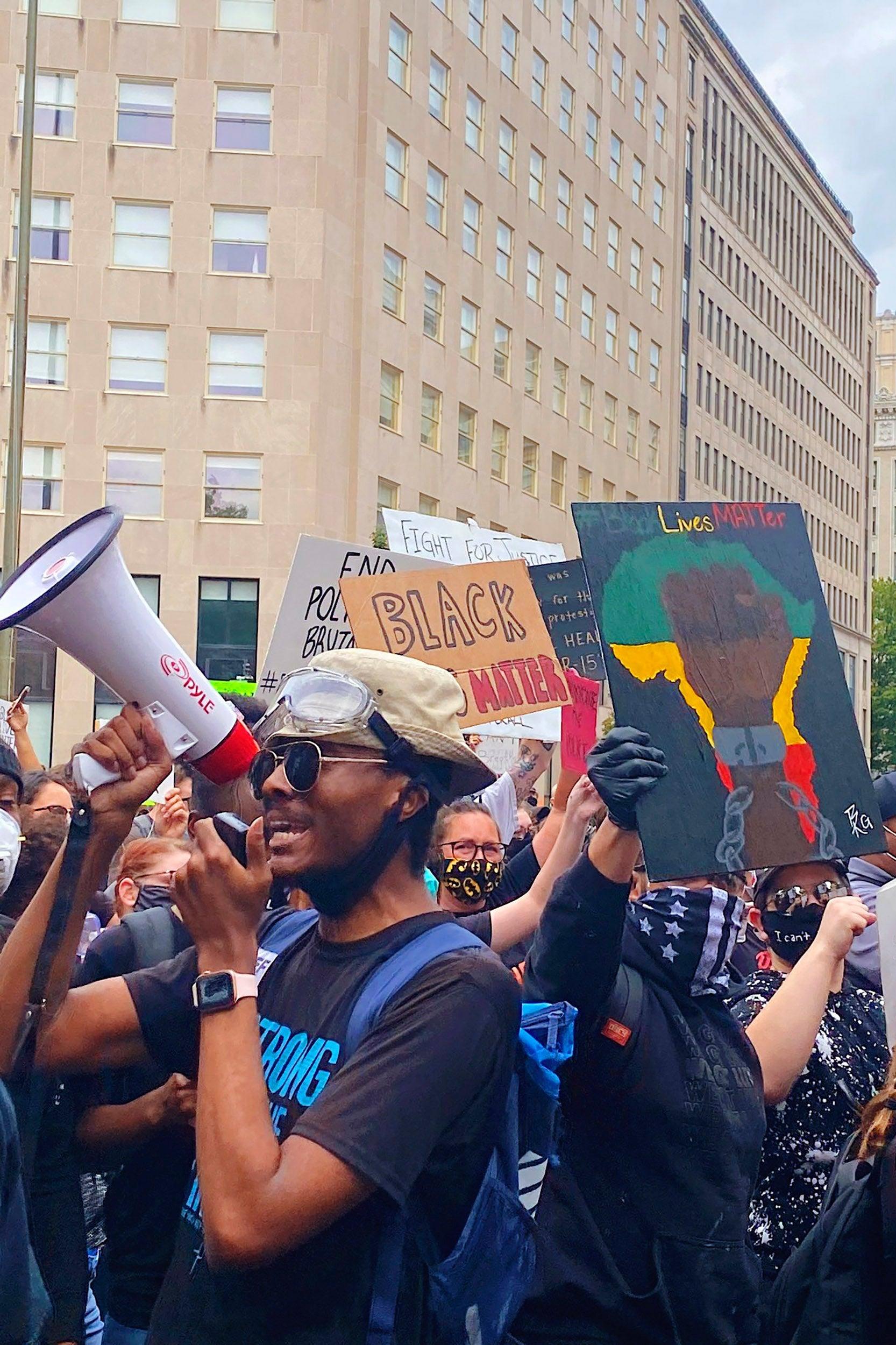 Glenn Foster holds bullhorn at protest.