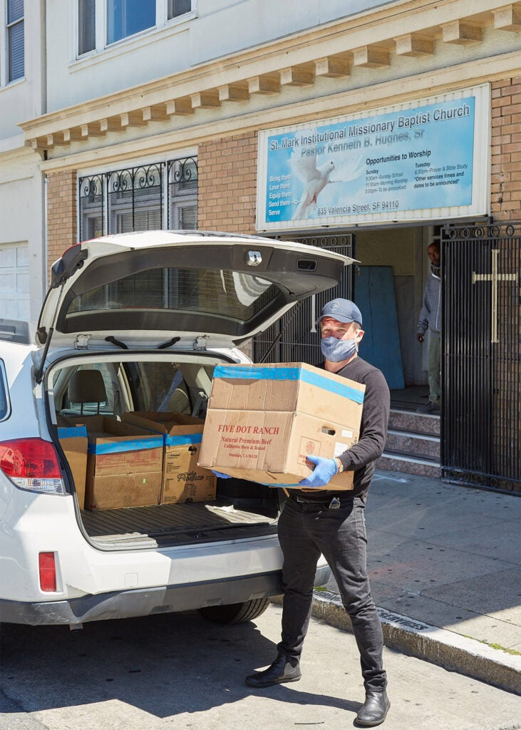 Loading boxes of food into a car.