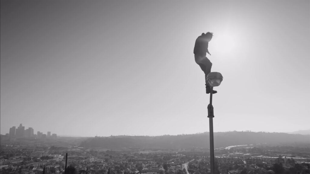 "Kendrick Lamar stands on lamppost towering over L.A. skyline in ""Alright"" video."