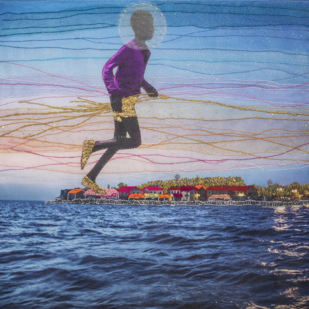 Embroidered photograph of boy floating over coastline.