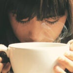 Person smelling a tasting a cup of tea.