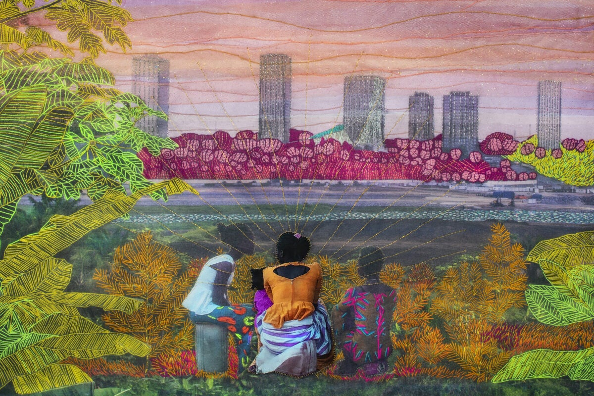Embroidered photo of three people looking at cityscape and sunset across body of water.