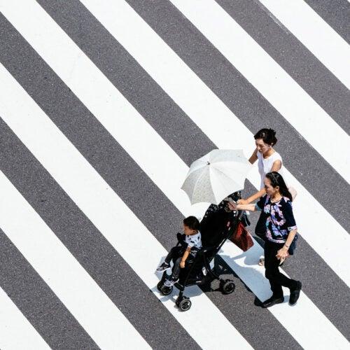 Asian family wzaalking across street.