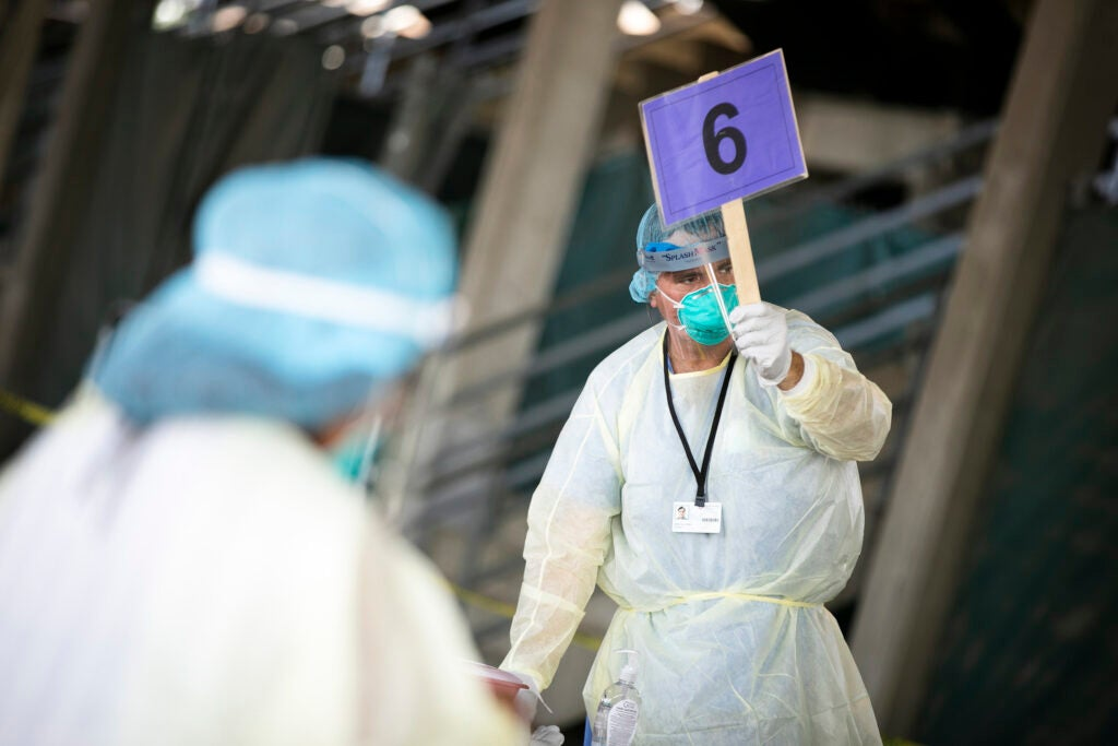 Nurse holds sign during COVID testing.