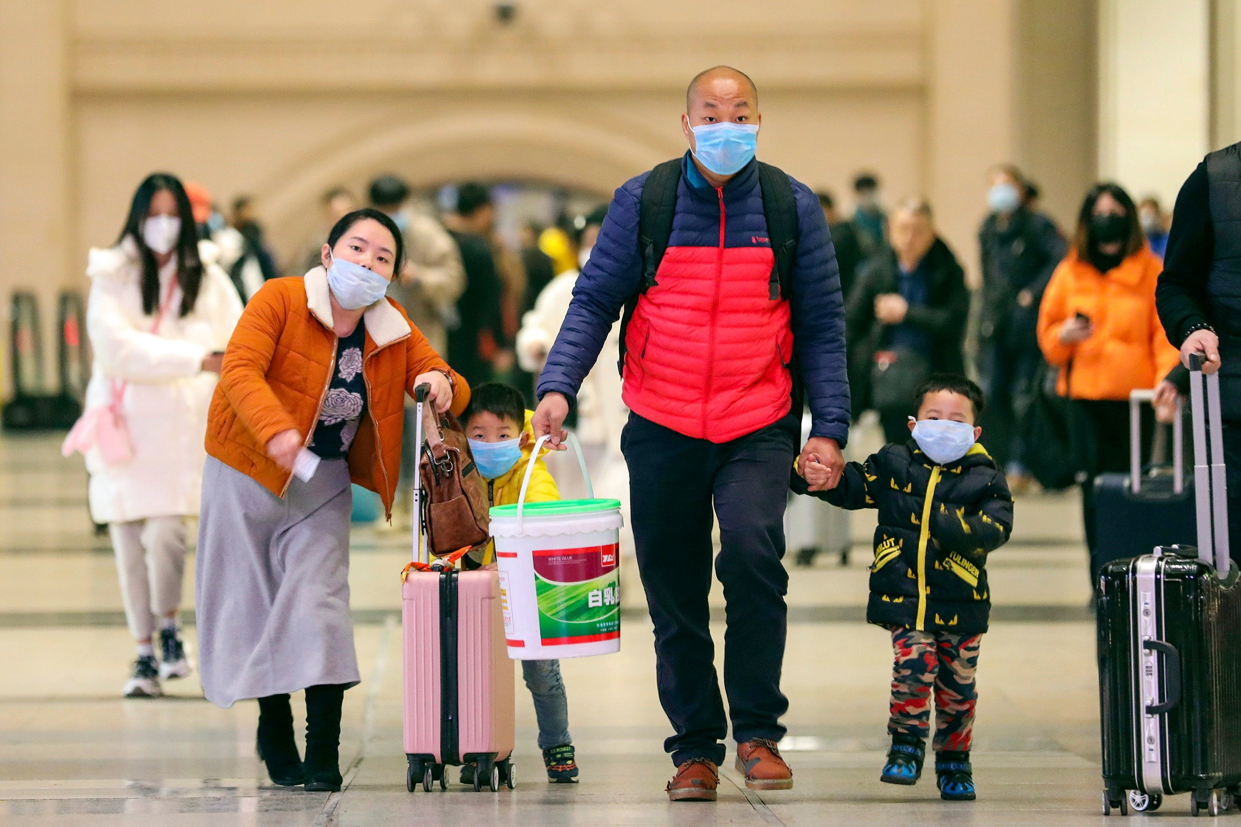 Masked travelers tote luggage in Wuhan in January.