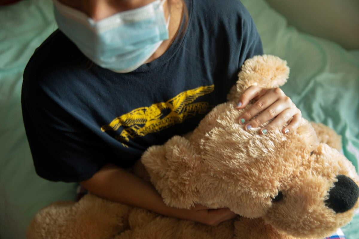Youngster in mask holding a teddy bear.