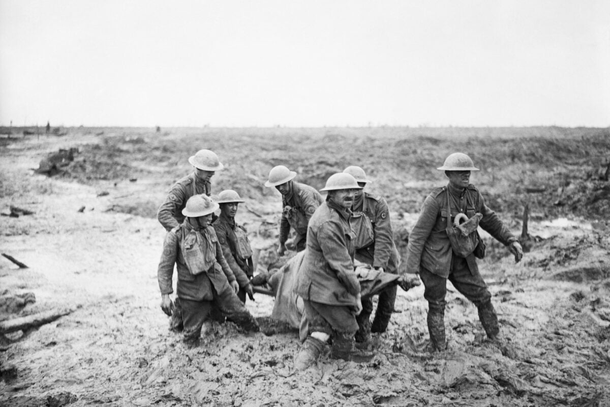 Carrying injured in hip-deep mud.