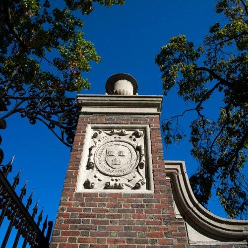 A veritas shield decorates a gate that encircles Harvard Yard.