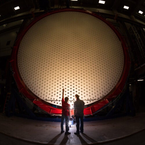 Two individuals stand in front of Magellan Mirror.