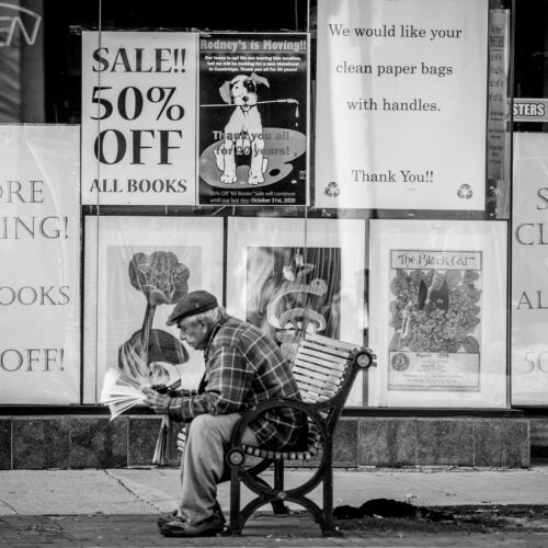 Man sitting on bench in front of store that is closing.
