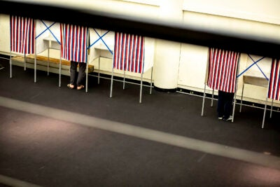 People in voting booths.