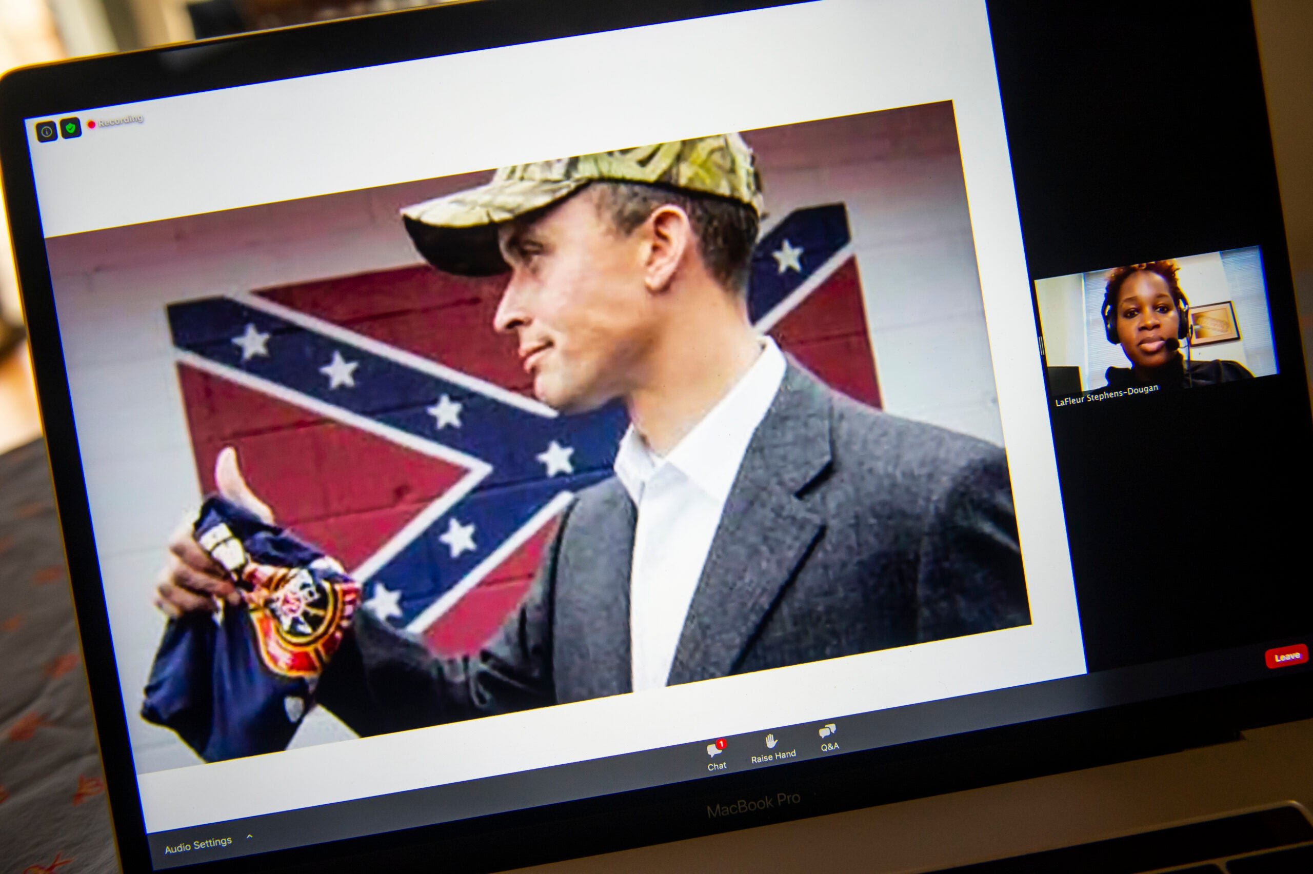 Politician with a Confederate flag behind him.