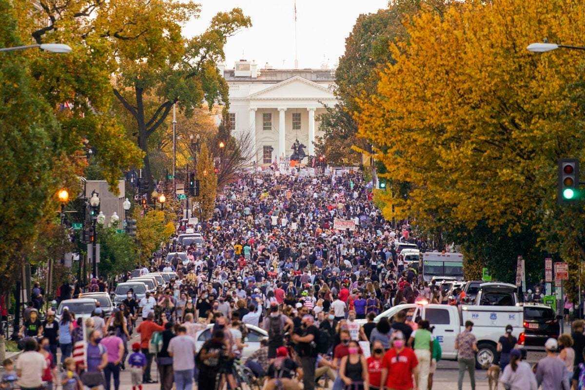 People gather along 16th street in front of the White House.