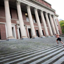 Man running steps at Widener Library.