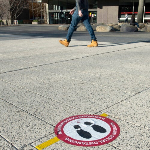 Social distance sticker on ground.