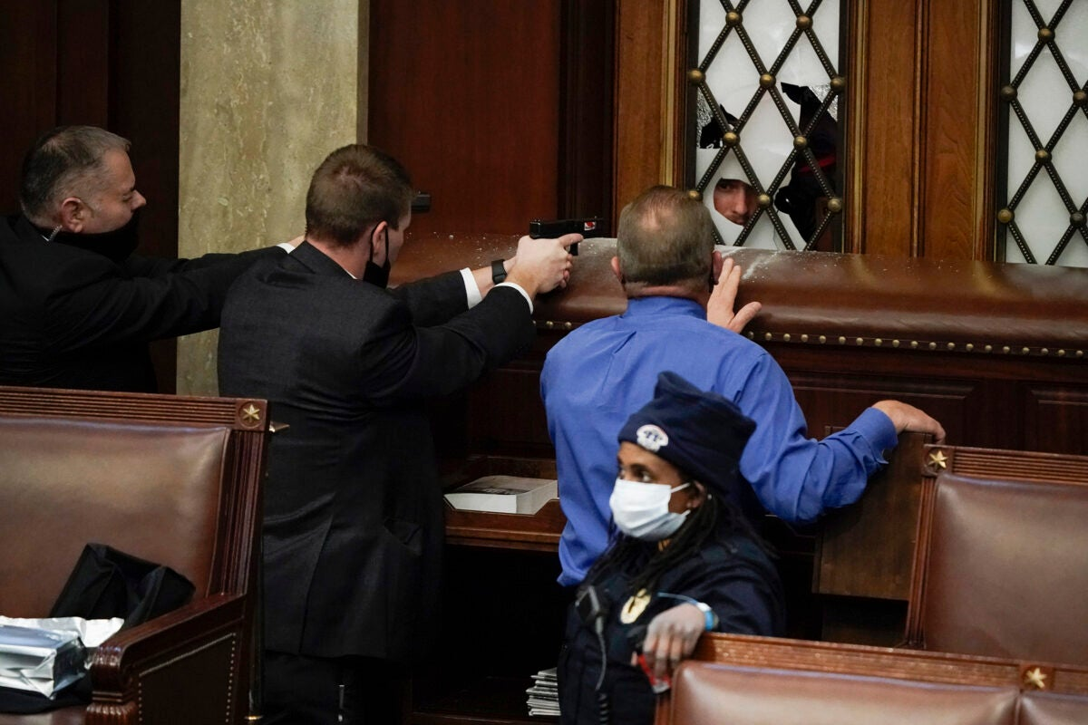 Police with guns drawn watch as rioters try to break into the House Chamber.