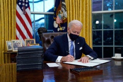 Joe Biden signs his first executive orders in the Oval Office.