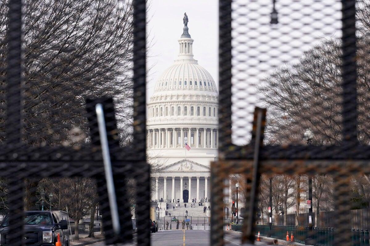 Capitol viewed through barricades.