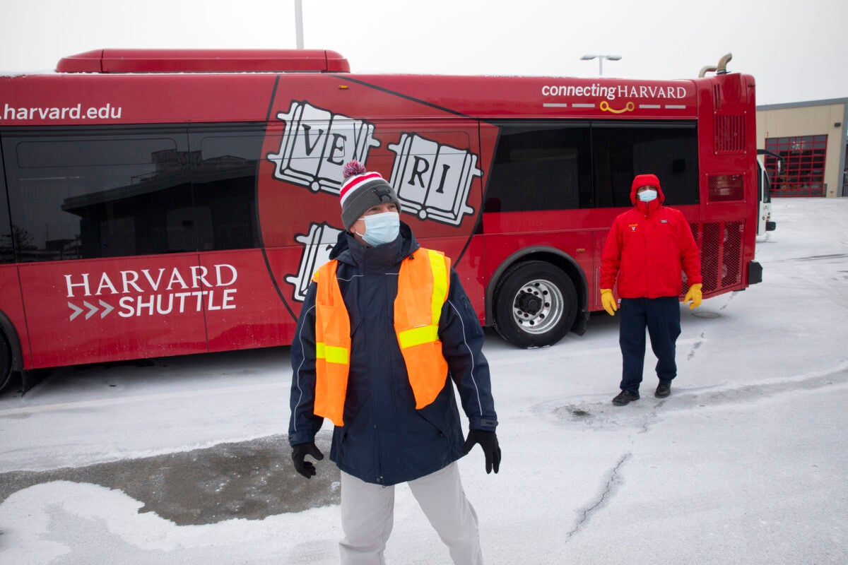 Two Harvard transportation people with bus.