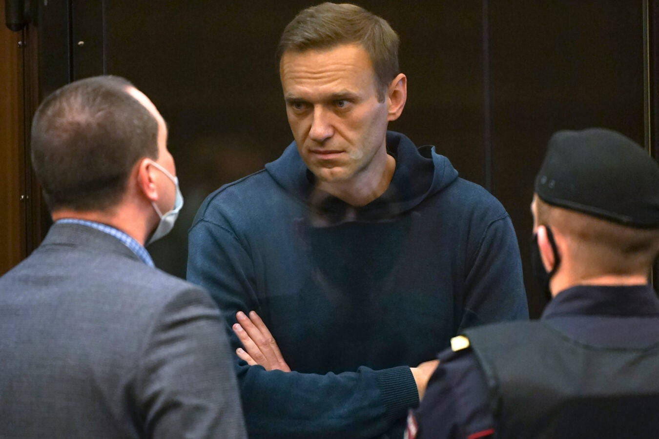 Alexei Navalny talks to one of his lawyers, left, while standing in the cage.