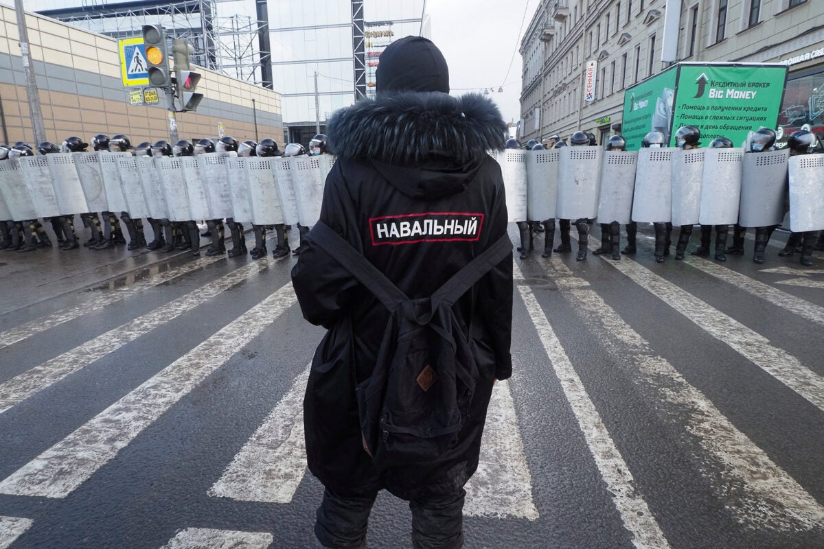 A man with a sign 'Navalny' on his back stands in front of riot policeme.