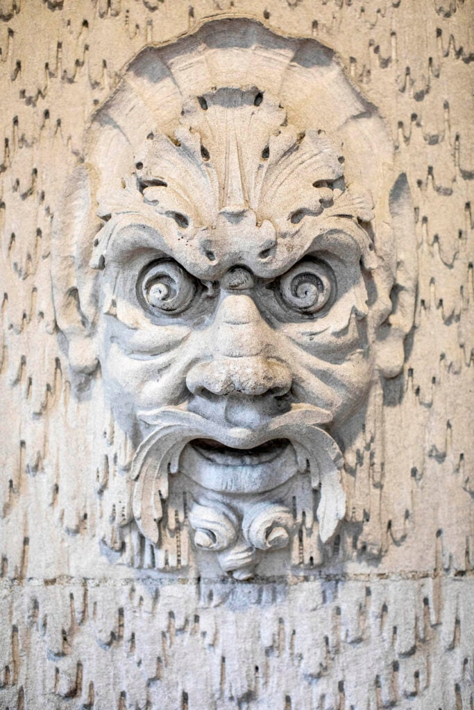 A faced carved in stone greets visitors at Randolph Hall's Westmorly Court entrance.