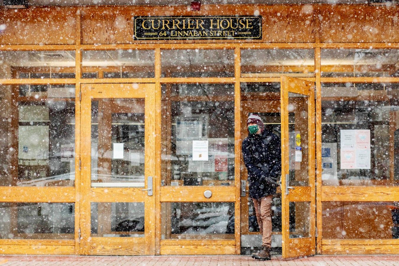 A student leaving Currier's main entrance braves the snow.