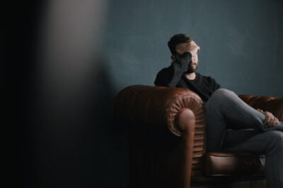 Man sitting on couch looking distressed.