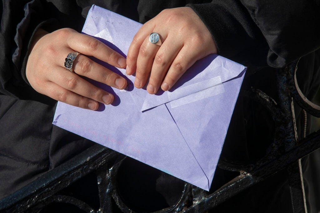 Two hands holding an envelope.