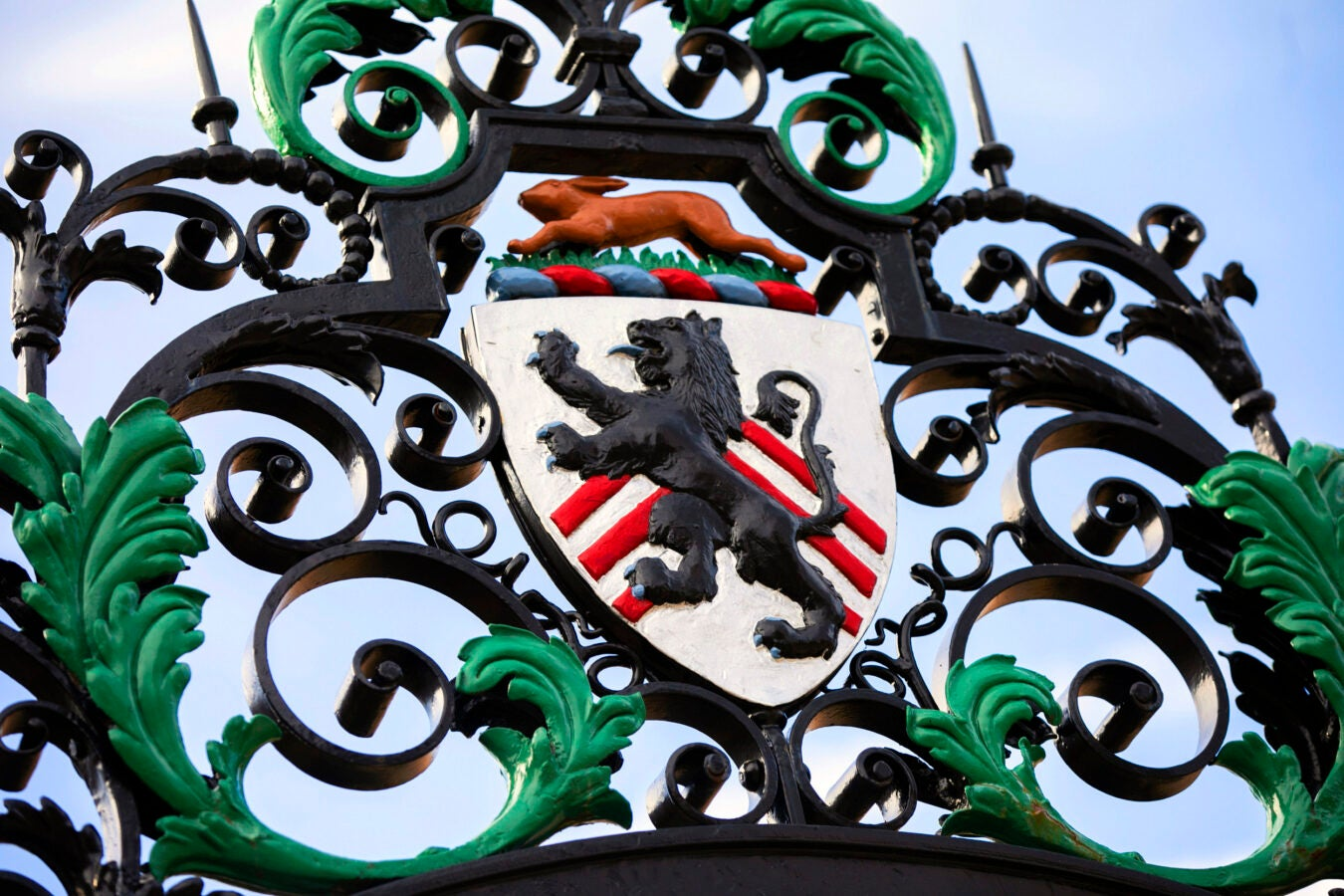 A rabbit leaps over the lion crest on the wrought-iron gate.