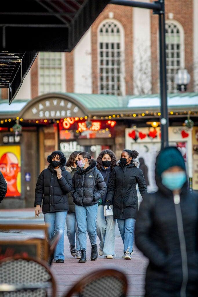 Masked pedestrians walk through Harvard Square.