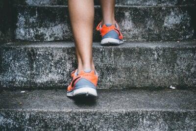 Two feet walking up concrete steps.
