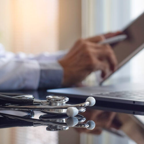 Male doctor in white coat hand holding and using modern digital tablet.