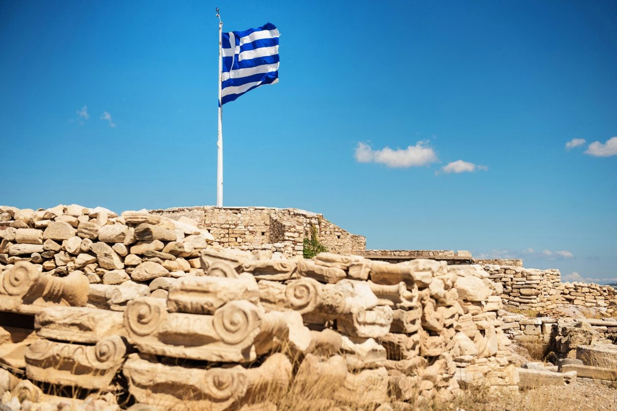 Waving flag of Greece on the top of the Acropolis Hill in Athens.