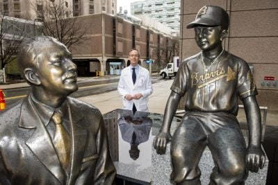 Patrick Ott, Associate Prof of Medicine at HMS and DFCI, stands by the statues of Dana-Farber founder Sidney Farber.