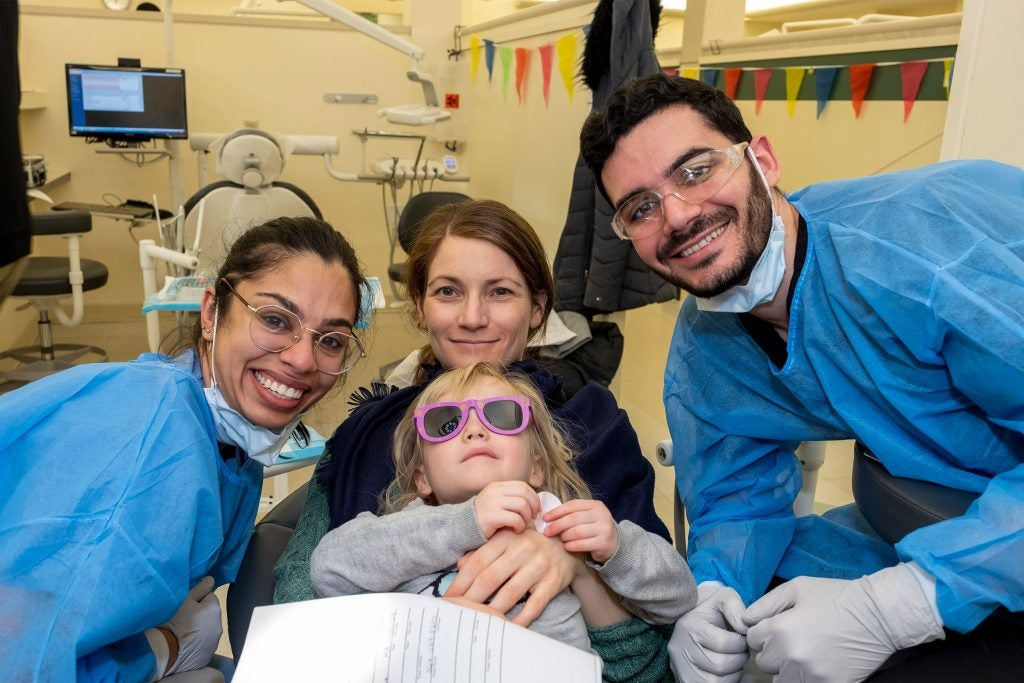 Ashiana Jivraj with other Dental School students and a young patient.