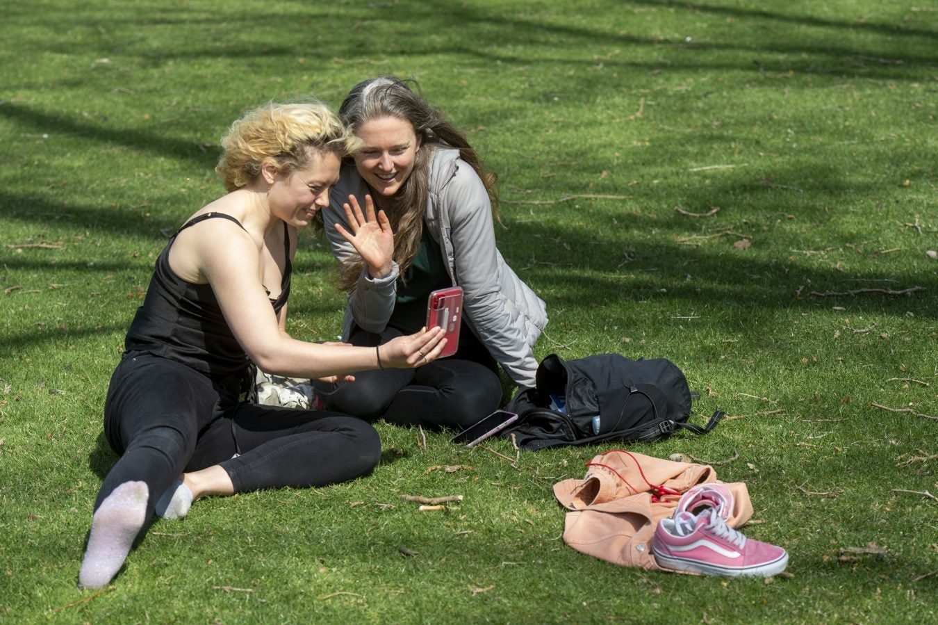 Grace Birch and Whitney McFadden FaceTime with a friend while relaxing on the HKS lawn adjacent to Memorial Drive.