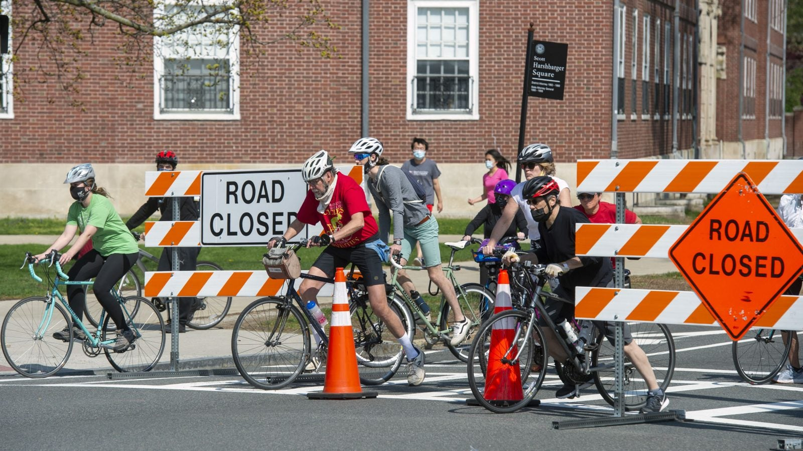 Bicyclists wait for the light at JFK Street next to a barricade on Mem Drive.