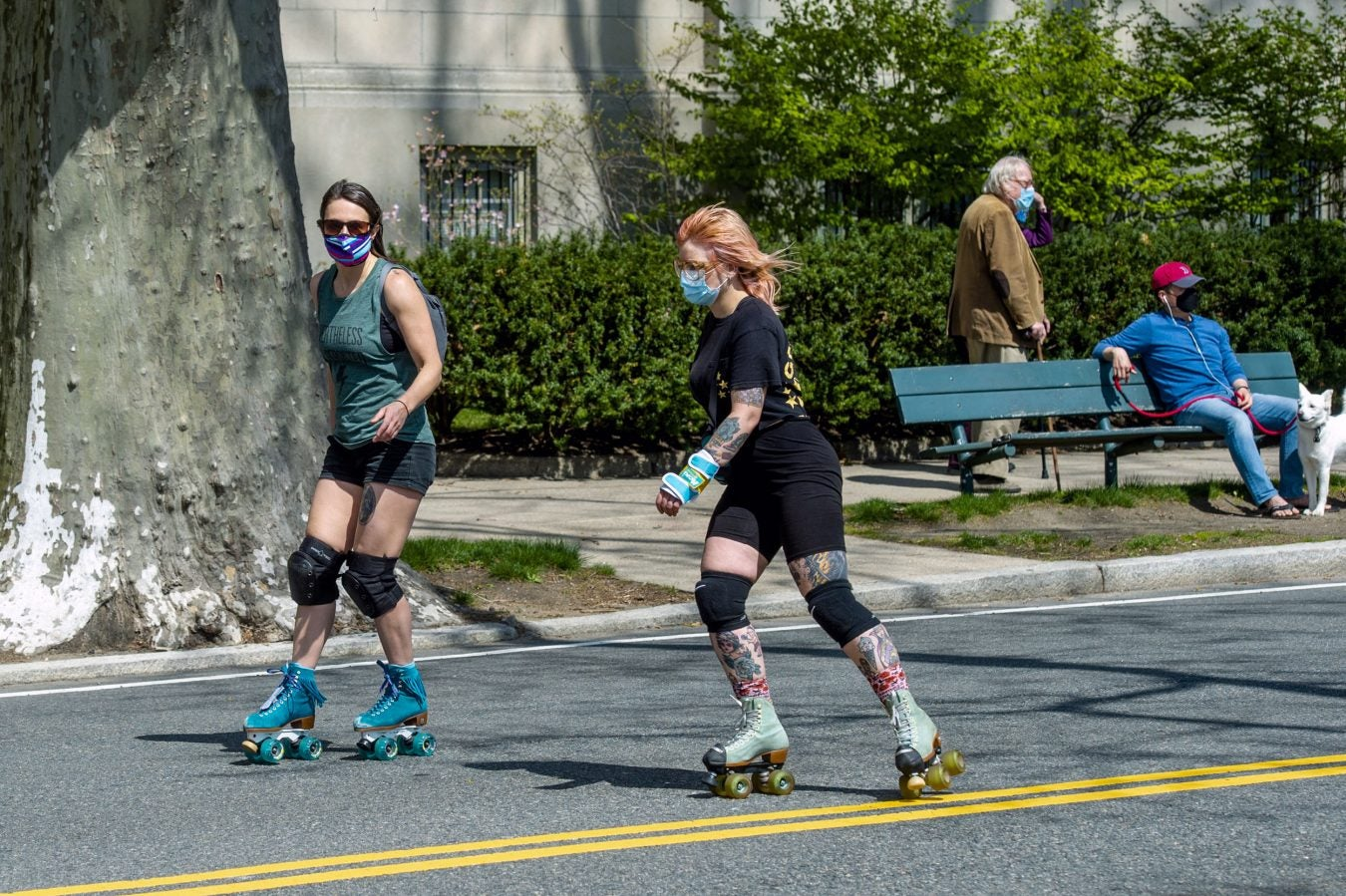 A couple of Rollerbladers glide past a walker and a man sitting on a bench with his dog.