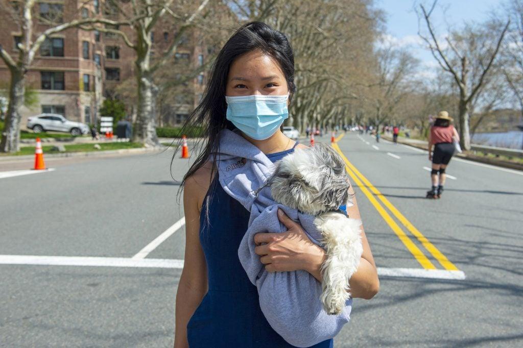 """Joon You cuddles her shih tzu """"Papi"""" as she walks along Memorial Drive."""