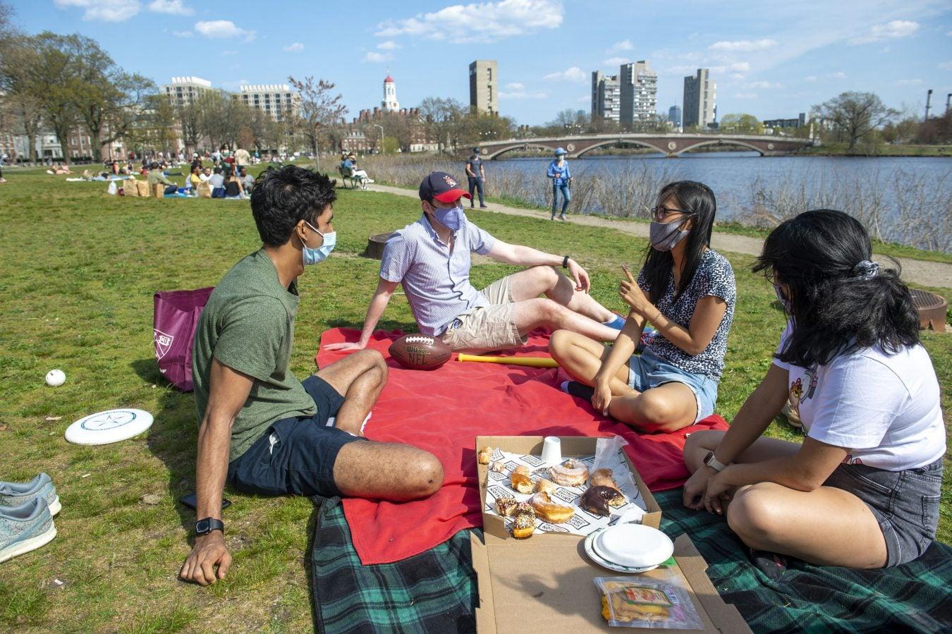 Devin Srivastava '21 (from left), Brooks Lambert, Nam Hyun Kim '21, and Ruth Jaensubhakij '22 gather on the grass between Memorial Drive and the river.