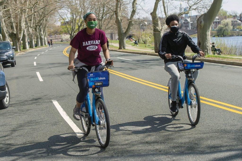 Daniela Diaz '23, left, and classmate Kilando Chambers '23 bike along the closed roadway on Memorial Drive.