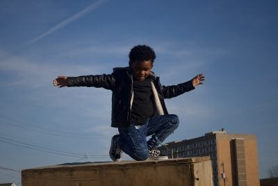 Child posing on a roof.