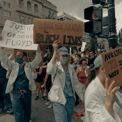Doctors holding up signs at a protest.